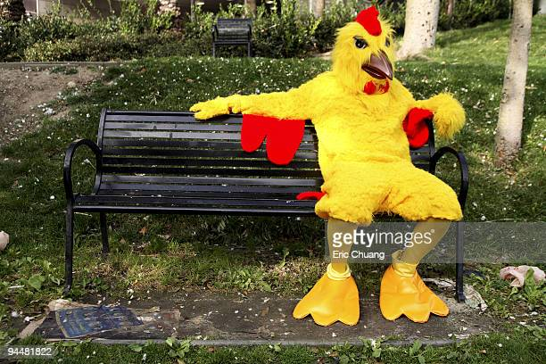 Person in chicken costume sitting on bench