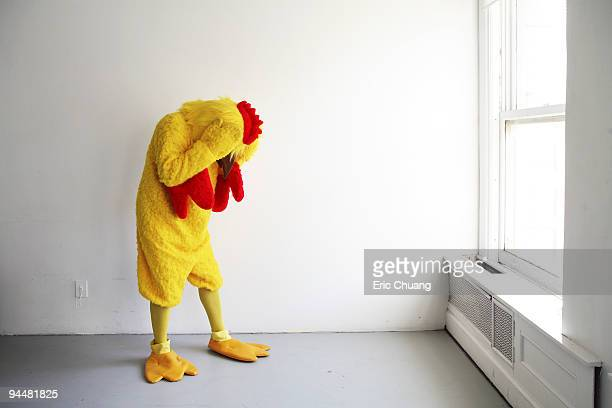Person in chicken costume standing in empty room
