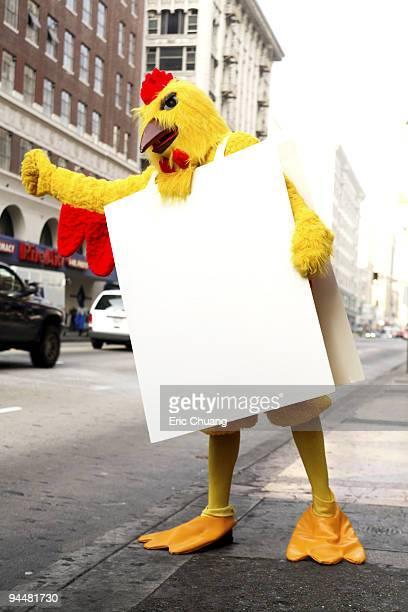 Person in chicken costume standing on sidewalk
