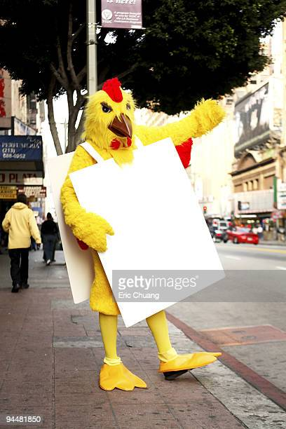 Person in chicken costume standing on sidewalk