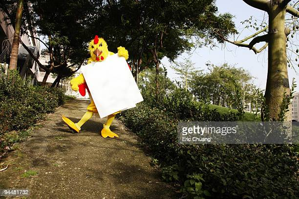 Person in chicken costume wearing signboard