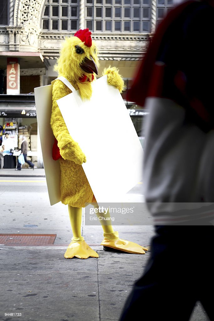 Person in chicken costume wearing signboard : Stock Photo