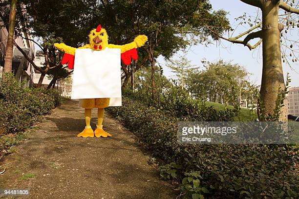 Person in chicken costume with blank sign