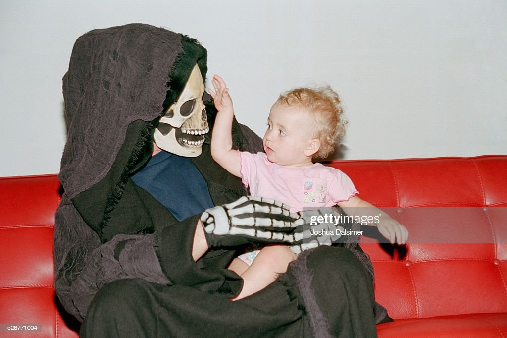 Person in costume holding baby : Stock Photo