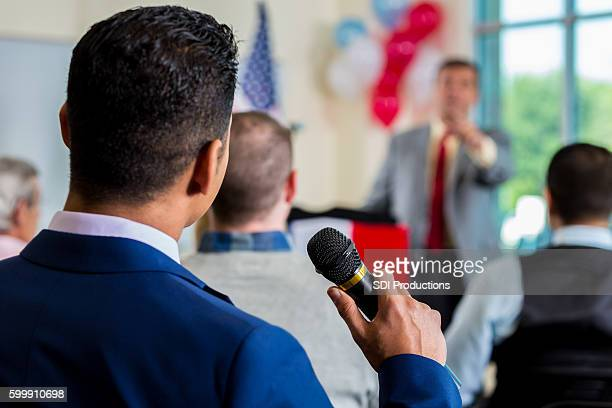 person in crowd asking question during town hall meeting - town hall meeting stock photos and pictures