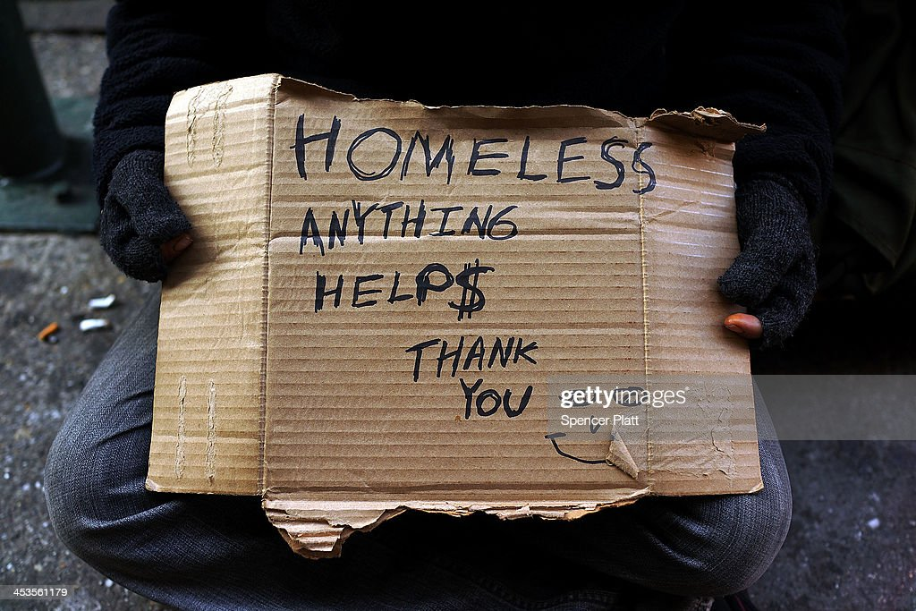 A person in economic difficulty holds a homemade sign asking for money along a Manhattan street on December 4, 2013 in New York City. According to a recent study by the by the United States Department of Housing and Urban Development, New York City's homeless population increased by 13 percent at the beginning of this year. Despite an improving local economy, as of last January an estimated 64,060 homeless people were in shelters and on the street in New York. Only Los Angeles had a larger percentage increase than New York for large cities.