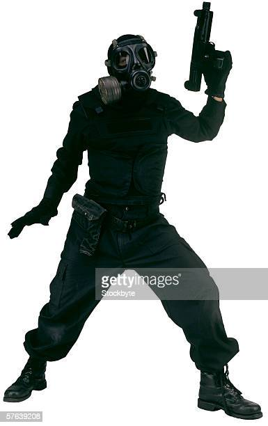 person in full black clothing wearing a gas mask holding a gun - cargo pants stock photos and pictures