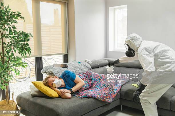 person in full hazmat suit and face mask removing tissue from sleeping man - handkerchief stock pictures, royalty-free photos & images