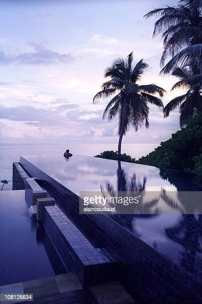 Person in Infinity Pool at Sunset on Seychelles Islands