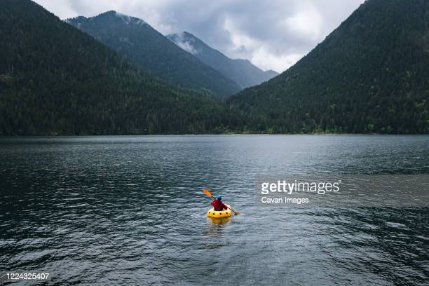 person in kayak paddling on lake towards mountains - olympic park stock pictures, royalty-free photos & images