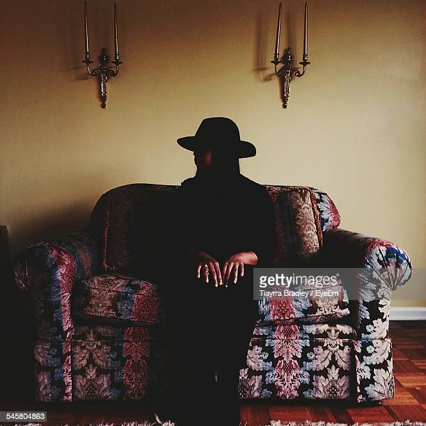 Person In Mask Sitting On Sofa At Home