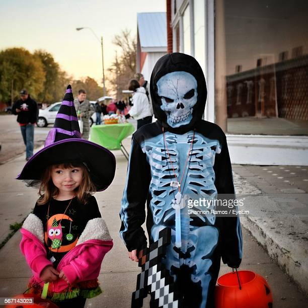 Person In Monster Costume Standing By Cute Girl On Footpath During Halloween