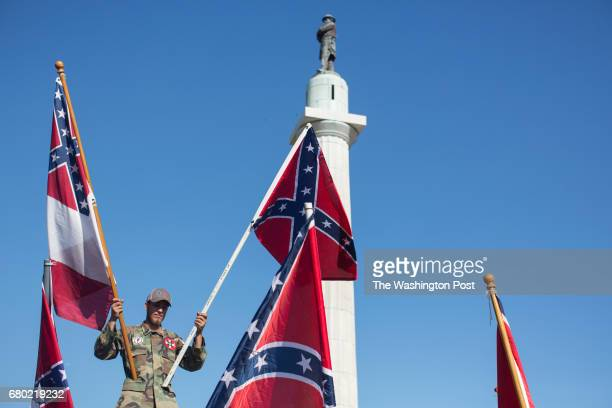 A person in opposition to the removal of monuments to the Confederacy holds confederate flags against the Robert E Lee statue in New Orleans Louisiana