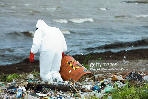 Person in protective suit carrying barrel of hazardous waste on polluted shore