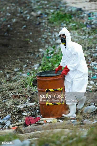 Person in protective suit carrying barrel of hazardous waste