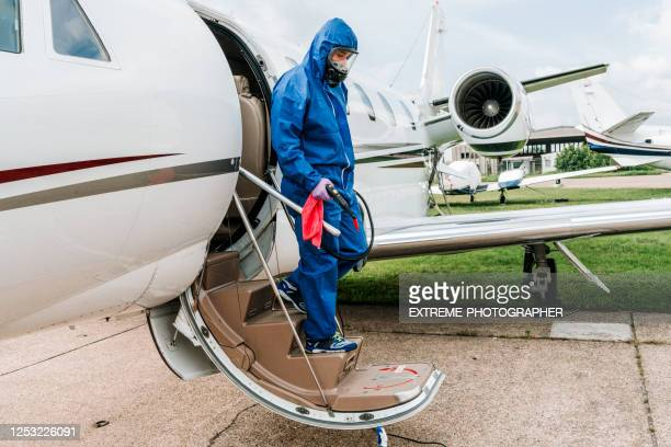 a person in protective work suit disembarking a private jet parked on an airport runway during covid-19 pandemic - department of health stock pictures, royalty-free photos & images