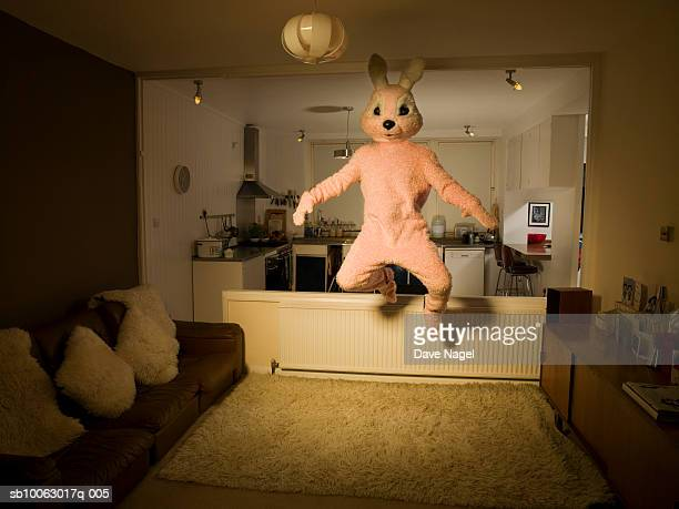 person in rabbit costume jumping in room - rabbit animal stock pictures, royalty-free photos & images