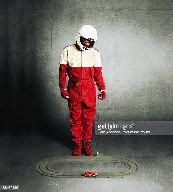 Person in racing gear playing with remote control car