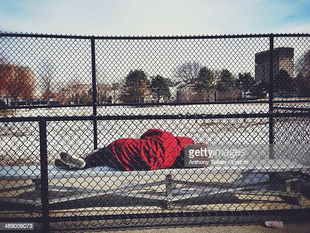 Person in red hood jacket sleeping on outdoor bench with fence in foreground