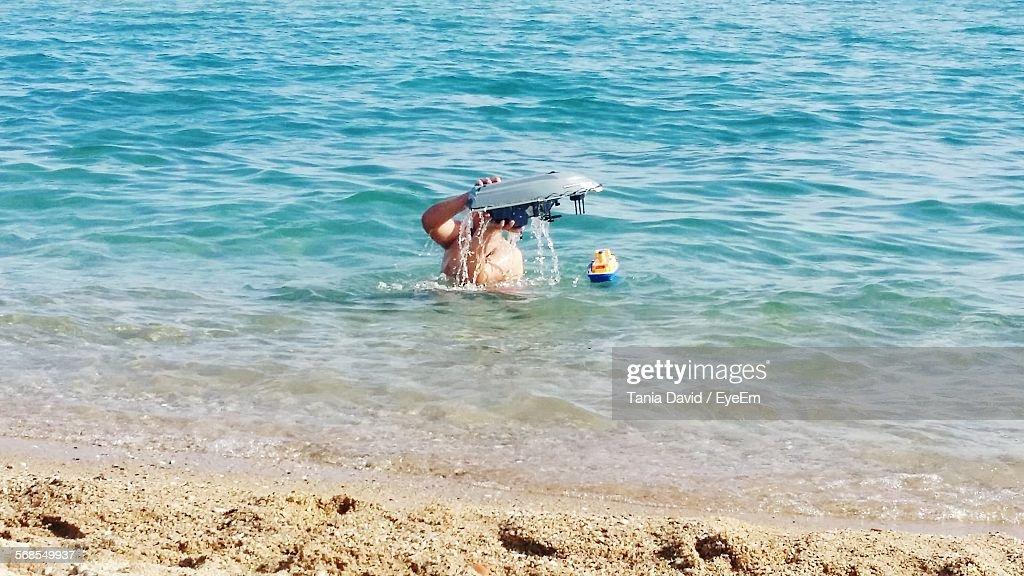 Person In Sea With Toy : Stock Photo