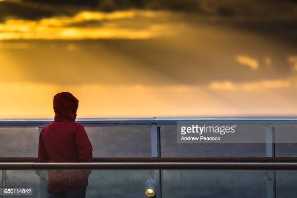 A person in silhouette stands watching sunset from the deck of a ship