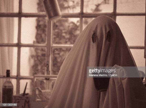 person in spooky costume holding mug while standing at home - fantome photos et images de collection