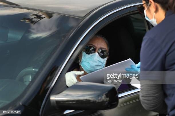A person in their car arrives to receive an unemployment application being given out by City of Hialeah employees in front of the John F Kennedy...