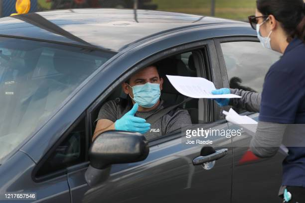 Person in their car arrives to receive an unemployment application being given out by City of Hialeah employees in front of the John F. Kennedy...
