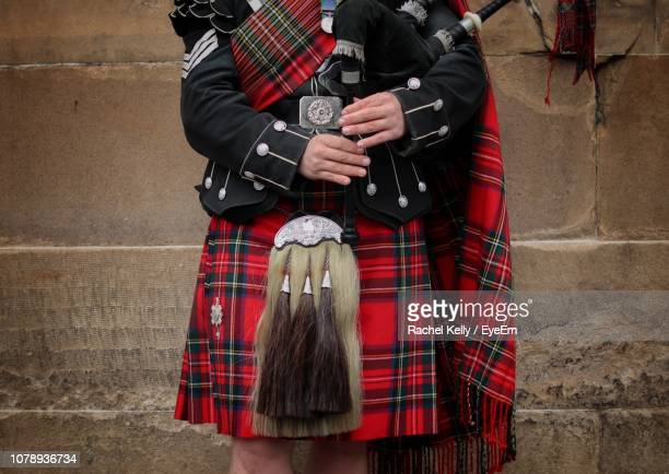 person in uniform standing against red wall - kilt stock photos and pictures
