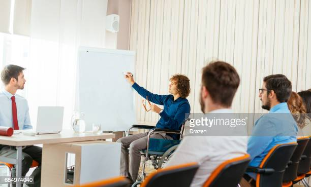 Person in wheelchair drawing project draft on flip chart