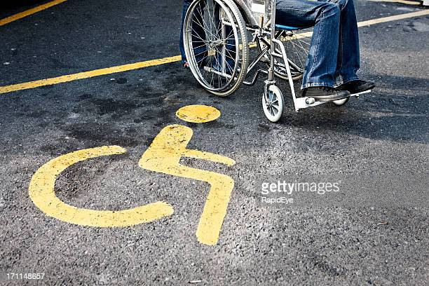 person in wheelchair next to a disabled parking sign - disabled access stock photos and pictures