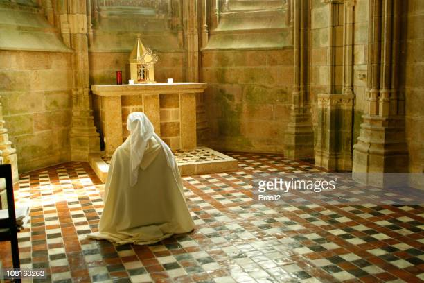 Person in White Robe Praying at Church Alter