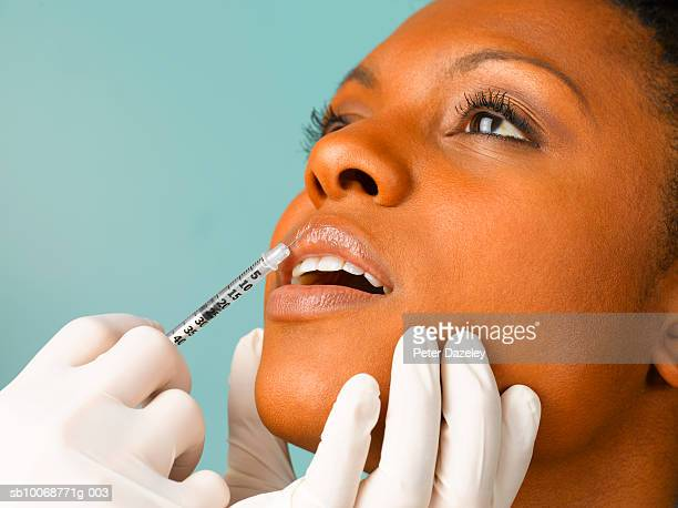 Person injecting botox into woman's lip, close up, studio shot