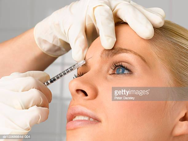 person injecting young woman's forehead with small syringe, close up, side view, studio shot - botox stock pictures, royalty-free photos & images