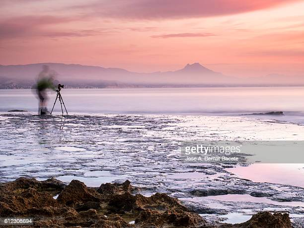 Person inside the water of the sea on the coast, extracting a photo of the colors of the dawn