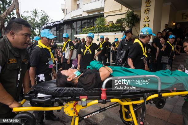 A person is carried away from the crowd on a stretcher by an by emergency medical team as as large numbers of Thai people line up on the streets for...
