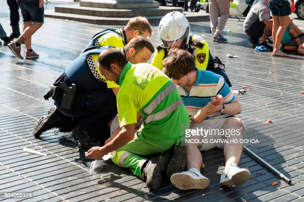 TOPSHOT A person is helped by Spanish policemen and two men after a van ploughed into the crowd killing at least 13 people and injuring around 100...