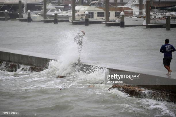 A person is hit by a wave churned up by approaching Hurricane Harvey on August 25 2017 in Corpus Christi Texas Hurricane Harvey has intensified into...