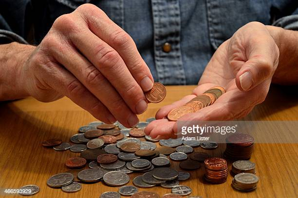 Person is seen counting money, cashing up, counting their savings/pension/disposable income/finances... They are holding a 1p coin in their hands...