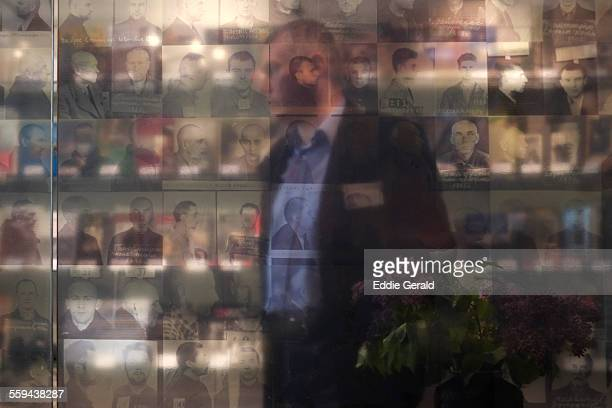 Vilnius LITHUANIA 1452015 A person is seen through mug shots of prisoners at the former KGB prison now the museum of Genocide in Vilnius Files of KGB...