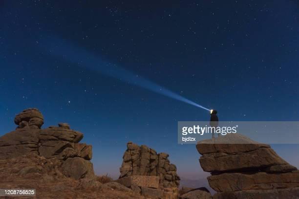 eine person steht mit scheinwerfern neben der milchstraßengalaxie. - weltraum und astronomie stock-fotos und bilder