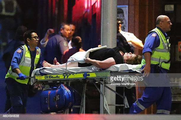 A person is taken out on a stretcher from the Lindt Cafe Martin Place following a hostage standoff on December 16 2014 in Sydney Australia Polie...