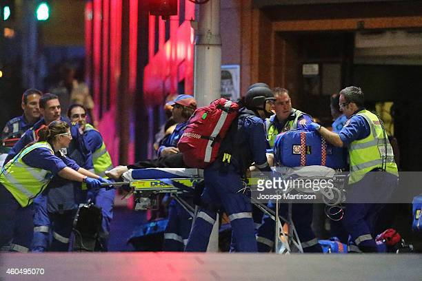 A person is taken out on a stretcher from the Lindt Cafe Martin Place following a hostage standoff on December 16 2014 in Sydney Australia Police...