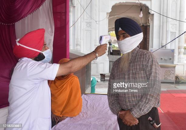 Person is thermal screened before entering the Golden Temple, on June 7, 2020 in Amritsar, India. Places of worship are set to reopen from tomorrow.