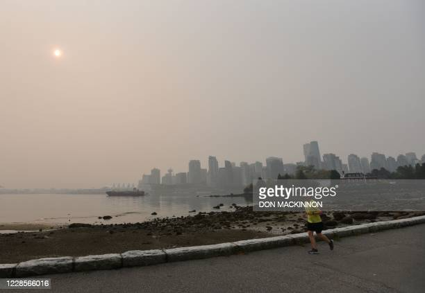 A person jogs along the Stanley Park seawall in Vancouver Canada with a view of the skyline under a heavy smog from clouds and smoke due to forest...