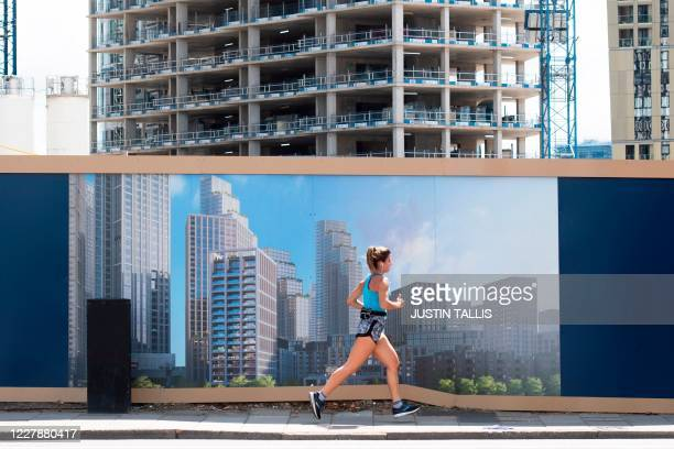 Person jogs past advertising boards by the One Nine Elms development site in south west London on August 2, 2020. - Plans for a shake-up of a...