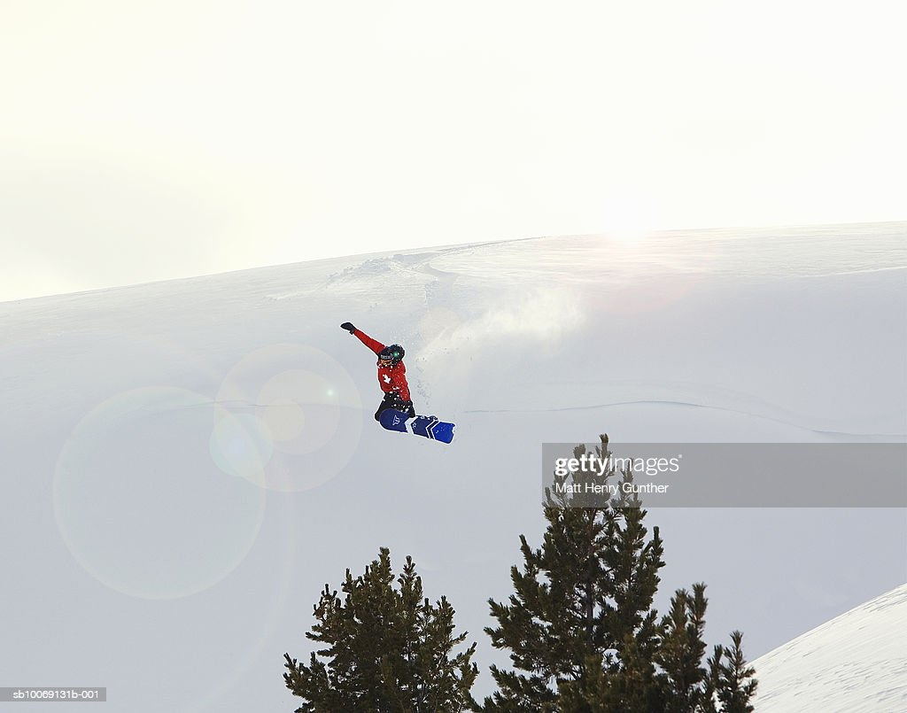 Person jumping in mid-air on snowboard : Stockfoto