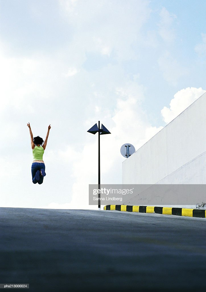 Person jumping in the middle of road : Stockfoto