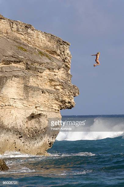 Person jumping into ocean from cliff
