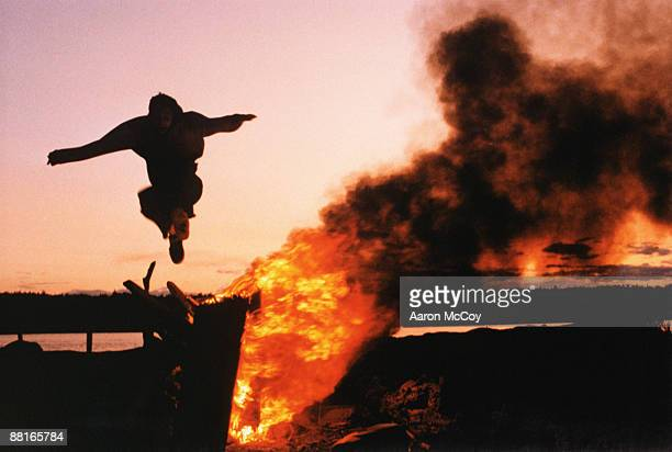 Person jumping over bonfire